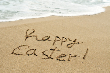 happy easter written in the sand of a beach