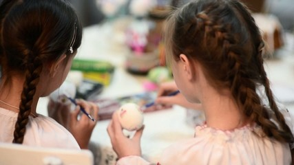 Two girls painting Easter eggs