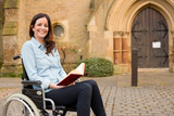 young woman in a wheelchair reading a bible outside a church