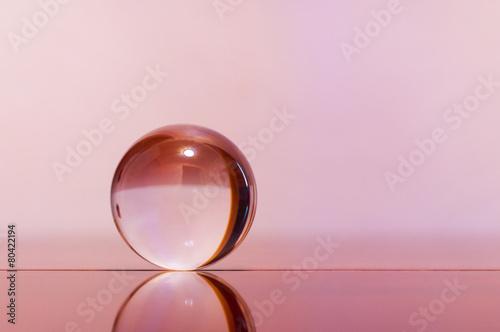 Szklana przejrzysta piłka na świetle - różowy tło i lustro