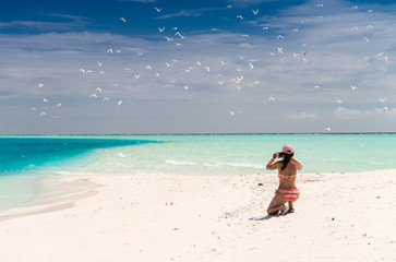 Woman photographing a stunning white beach with turquoise ocean