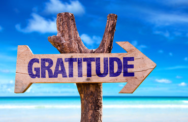Gratitude sign with a beach on background