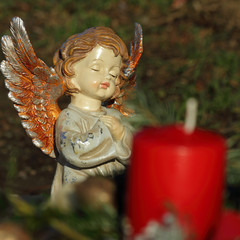little angelic ceramic  figurine and candle on catholic cemetery