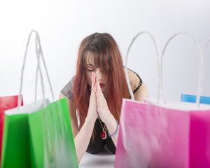 Young Woman Praying by Colorful Shopping Bags