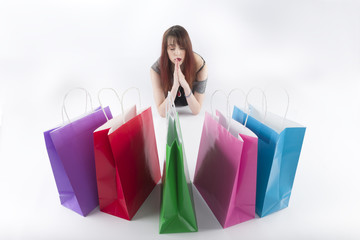 Woman in Praying Pose In Front of Shopping Bags