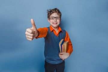 European-looking boy of ten years in glasses showing thumb up