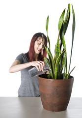Happy Woman Watering a Green Plant in a Pot