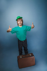 European-looking boy of  ten years in a hat holding a suitcase