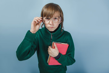 European-looking boy  of ten years in glasses holding a book on