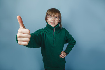 European-looking boy of ten years showing thumbs up on blue