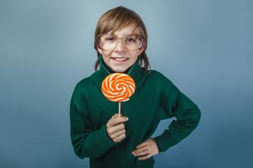 European-looking boy of ten years holding a lollipop on a blue