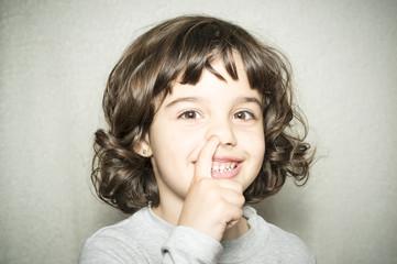 Niña con el dedo en la nariz
