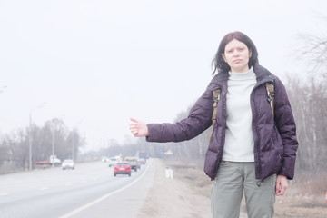 Traveler woman is catching a car hitchhiking