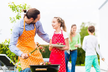Father and daughter barbecue together