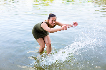 Woman romping cheerful in lake water