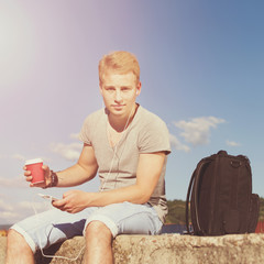 Young man with takeaway coffee and smart phone outdoors