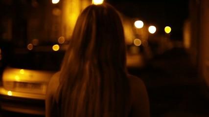 Woman walks down dark street alone at night