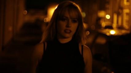 Blonde woman walks down dark street alone