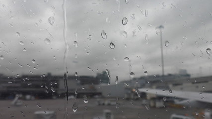 Airport view through wet airplane window