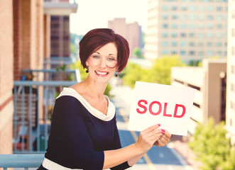 Real estate agent holding sold sign isolated on city background