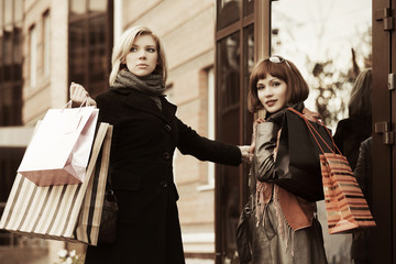 Two young fashion women with shopping bags