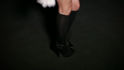 Dancing females feet in leather boots in a dark room