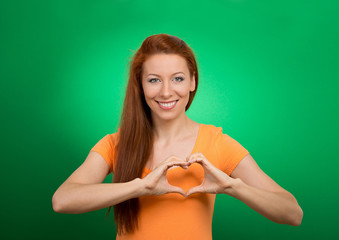 happy young woman making heart hands sign green background