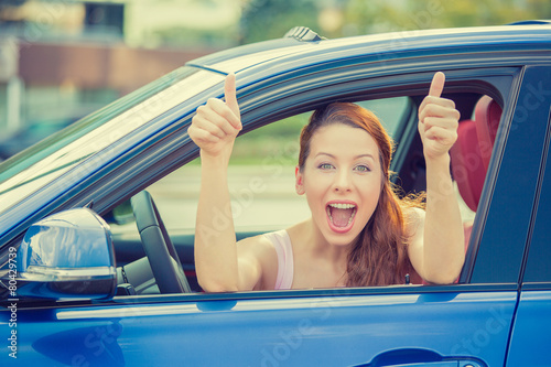 Leinwandbild Motiv driver happy smiling showing thumbs up sitting inside new car