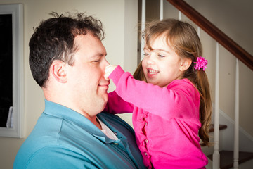 little girl being silly playing with her dad