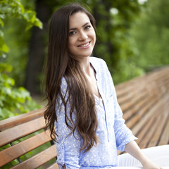 Brunette sitting on a bench