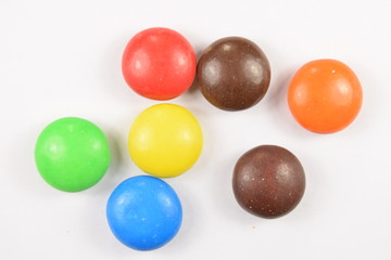 Colorful candies spread on white background.