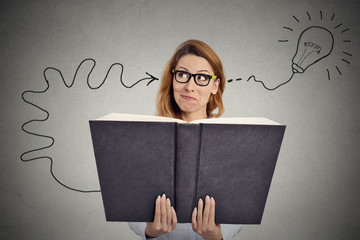 Woman reading a huge book has a good idea gray background