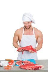 chef bodybuilder preparing large chunks of raw meat.