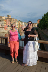 Two women on background of colorful houses in Girona, Spain.