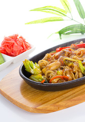 Udon with seafood and vegetables over white background
