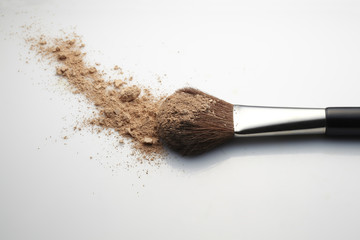 Makeup Brush with beige loose Face Powder on white background