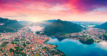Colorful summer sunrise on the city and lake Lecco