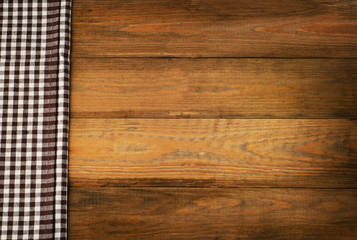 Brown checkered Tablecloth textile on a old wooden background