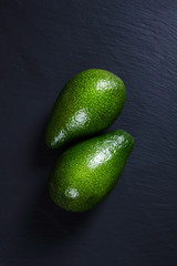 Two ripe avocados on a dark background