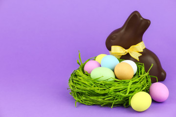 Happy Easter greeting card - eggs in nest with chocolate bunny