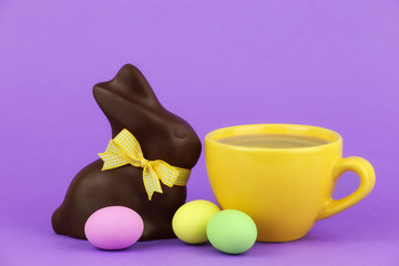Happy Easter concept - cappuccino with chocolate bunny and eggs
