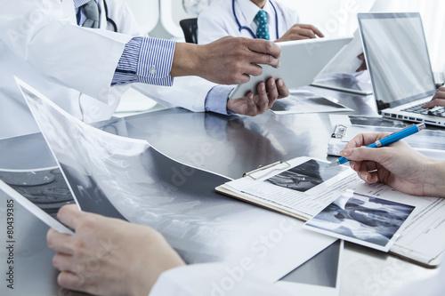 Leinwanddruck Bild Doctor looking at X-ray photo