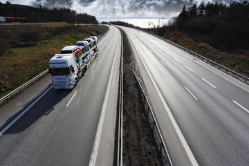 truck transporting new cars on a scenic highway, early evening