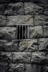 Barred window on wall made of stone blocks