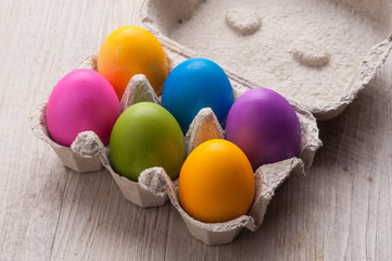 Uova sode pasquali colorate nel contenitore ecologico
