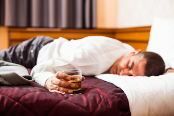 Businessman sleeping on a bed, holding glass of whisky
