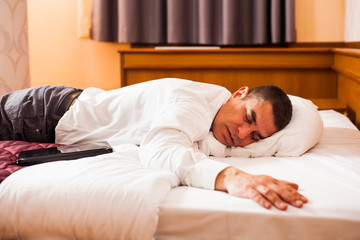 Tired businessman is sleeping on a bed