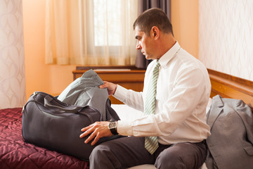 Businessman is packing luggage in hotel room