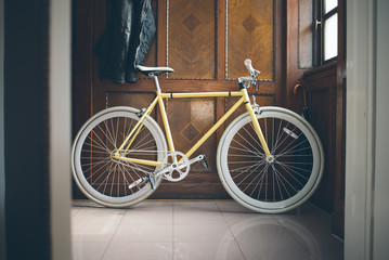 A yellow fixed-gear bicycle (also called fixie)  at home