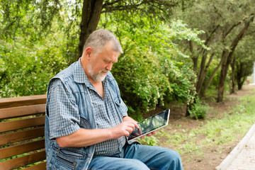 old man with tablet sitting on a bench